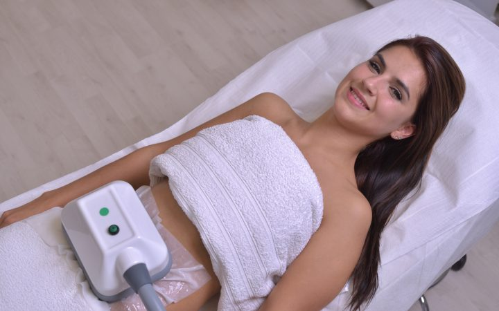 Beautiful young woman getting cryolipolyse treatment in cosmetic clinic